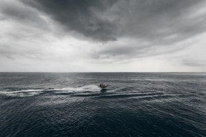 motor boat floating in sea in stormy day